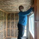 Gerry installing the glasswool batts for more insulation.